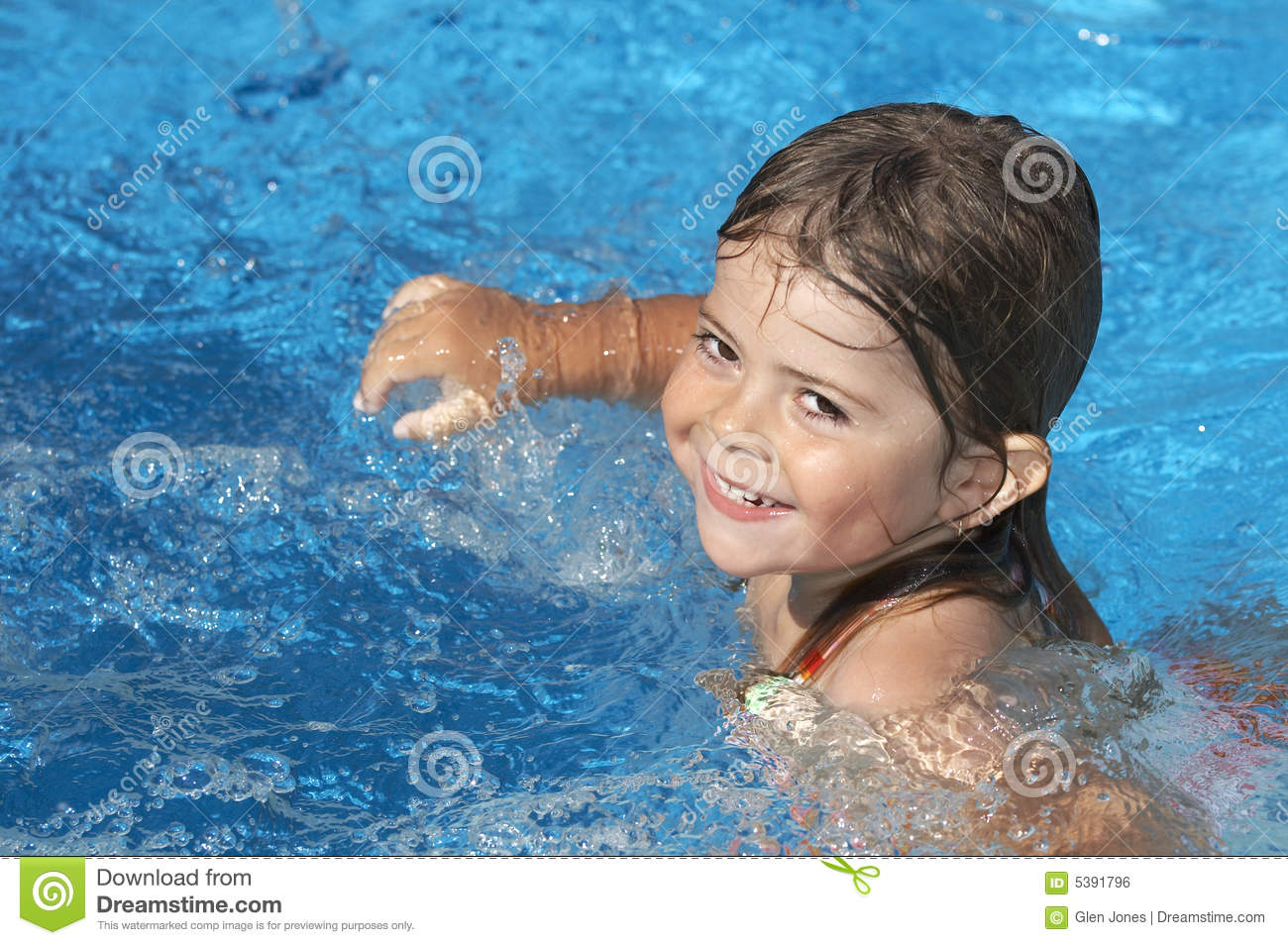 Cute little girl in pool water during the summer