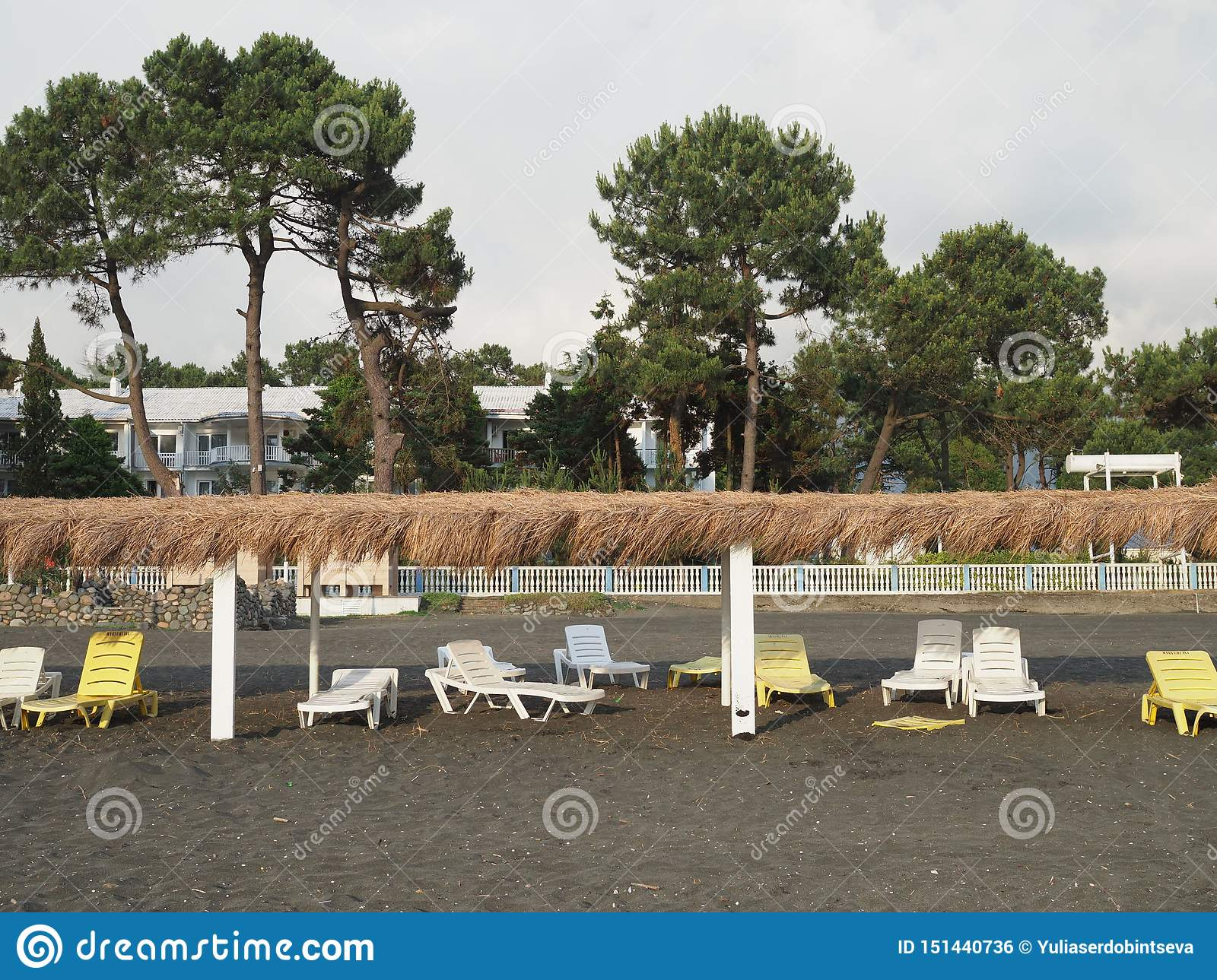 Summer, sun, deserted beach of the coast with sun loungers. Beach by the sea with empty deck chairs set in a row