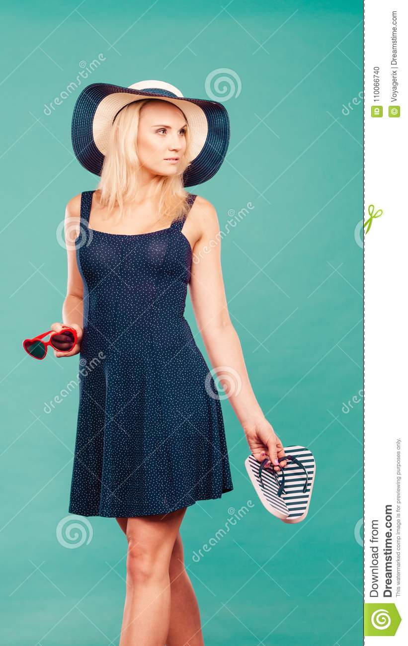 b942a90e0228b2 Summer trendy fashionable outfit ideas concept. Woman wearing short navy  dress sun hat holding flip flops and sunglasses.