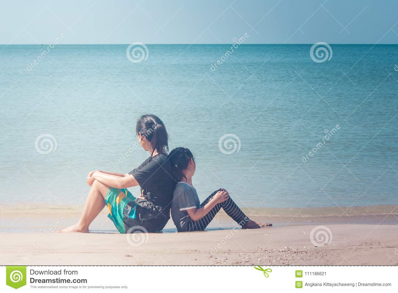 Summer Vacation and Holiday Concept : Happy family day trip at the sea, Woman and child sitting back to back relax on sand beach.