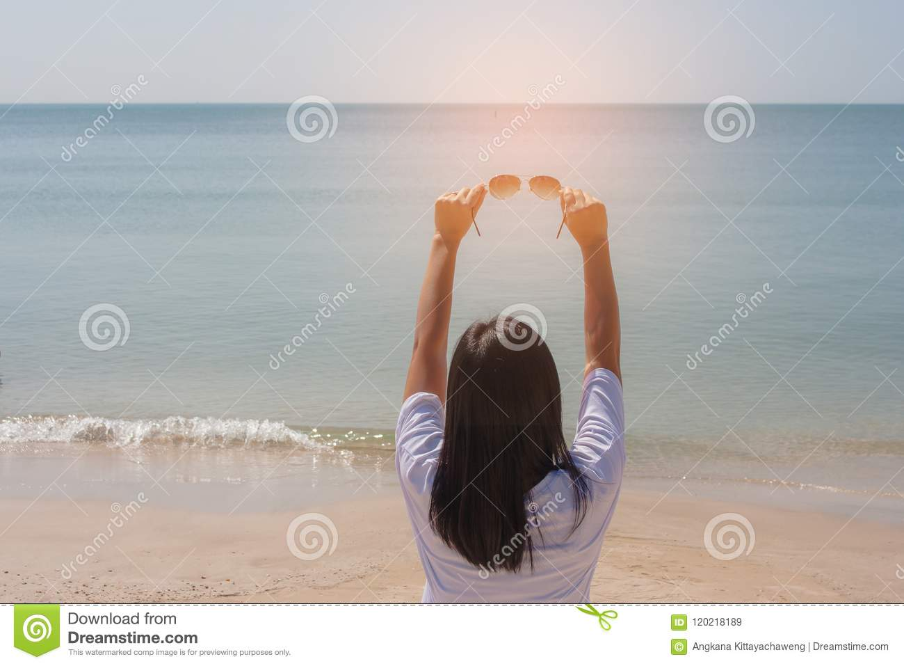 Summer Vacation and Holiday Concept : Woman standing on sand beach. She holding sunglasses in her hand.