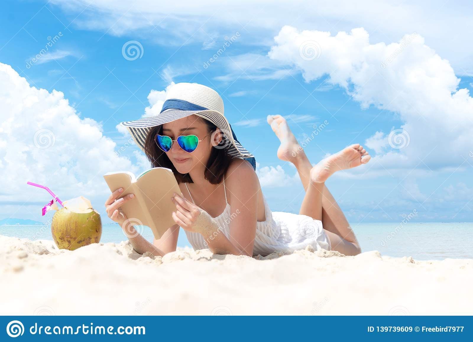 Summer Vacation. Smelling asian women relaxing and reading book on the beach, so happy and luxury in holiday summer, outdoors blue