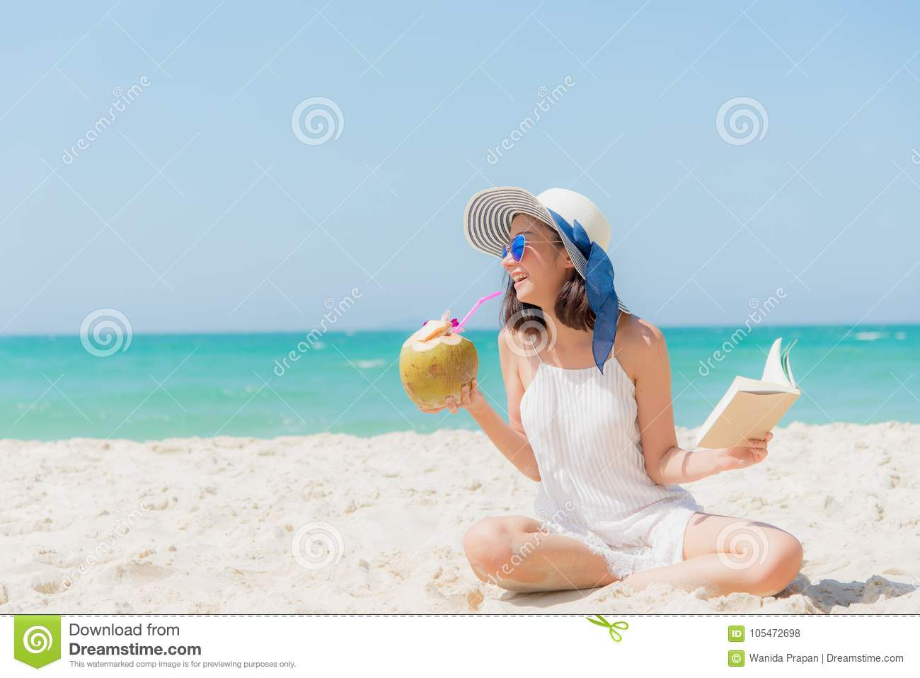 Summer Vacation. Smelling asian women relaxing, reading book and drinking coconut cocktail on the beach,