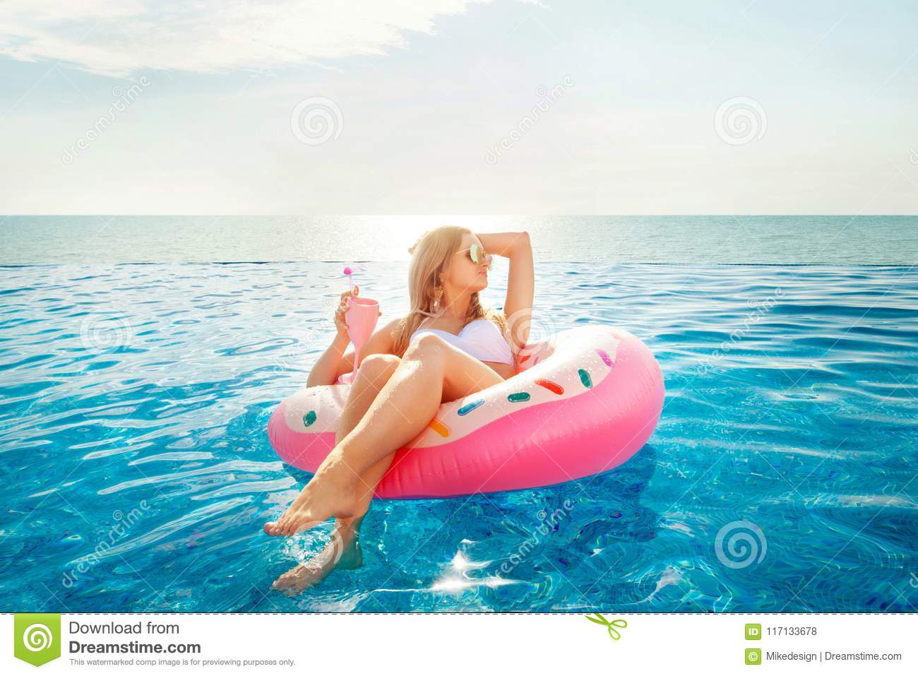 Summer Vacation. Woman in bikini on the inflatable donut mattress in the SPA swimming pool.