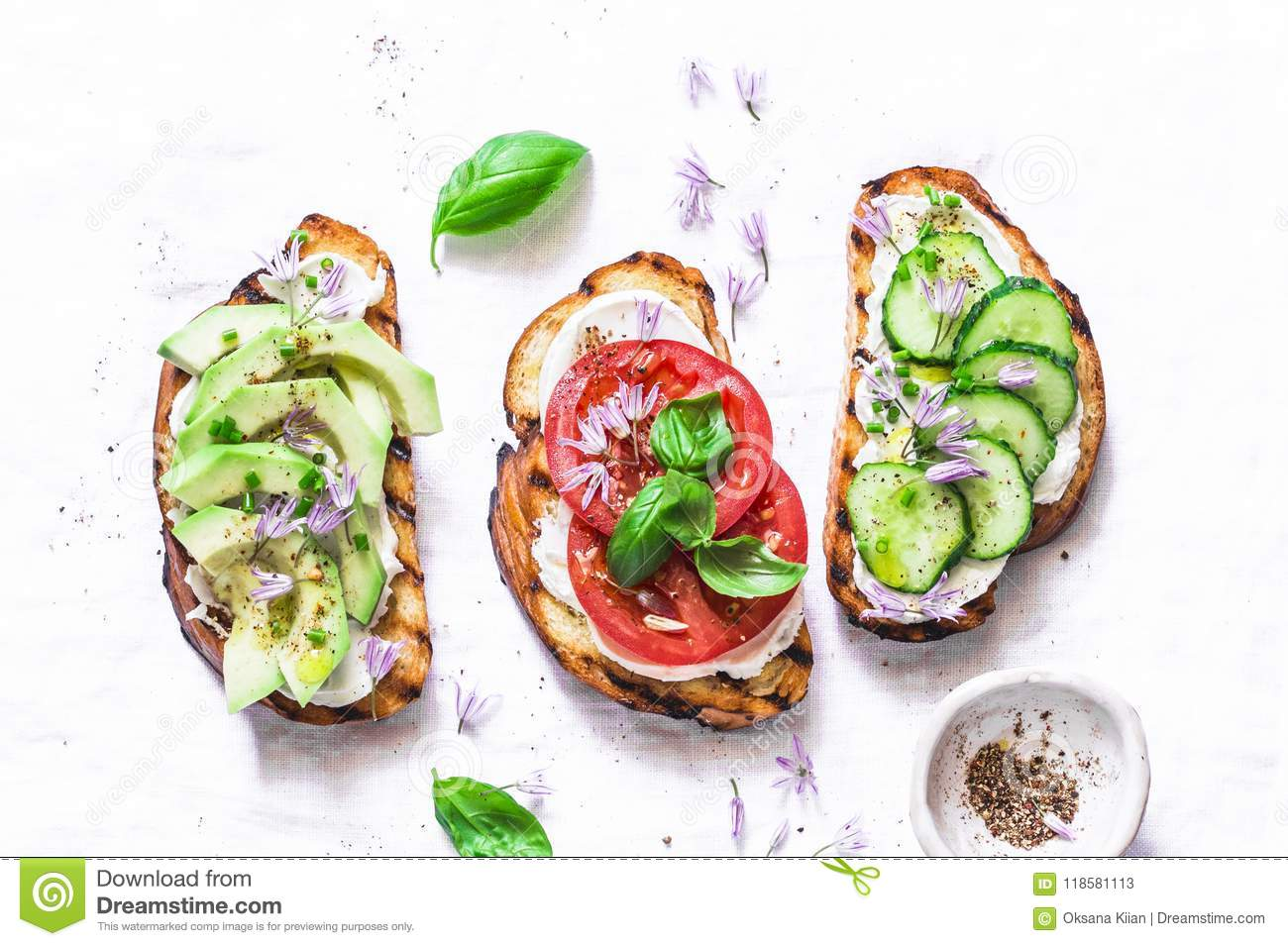 Summer variations of sandwiches - with cream cheese, avocado, tomato and cucumber on a light background, top view. Healthy diet fo