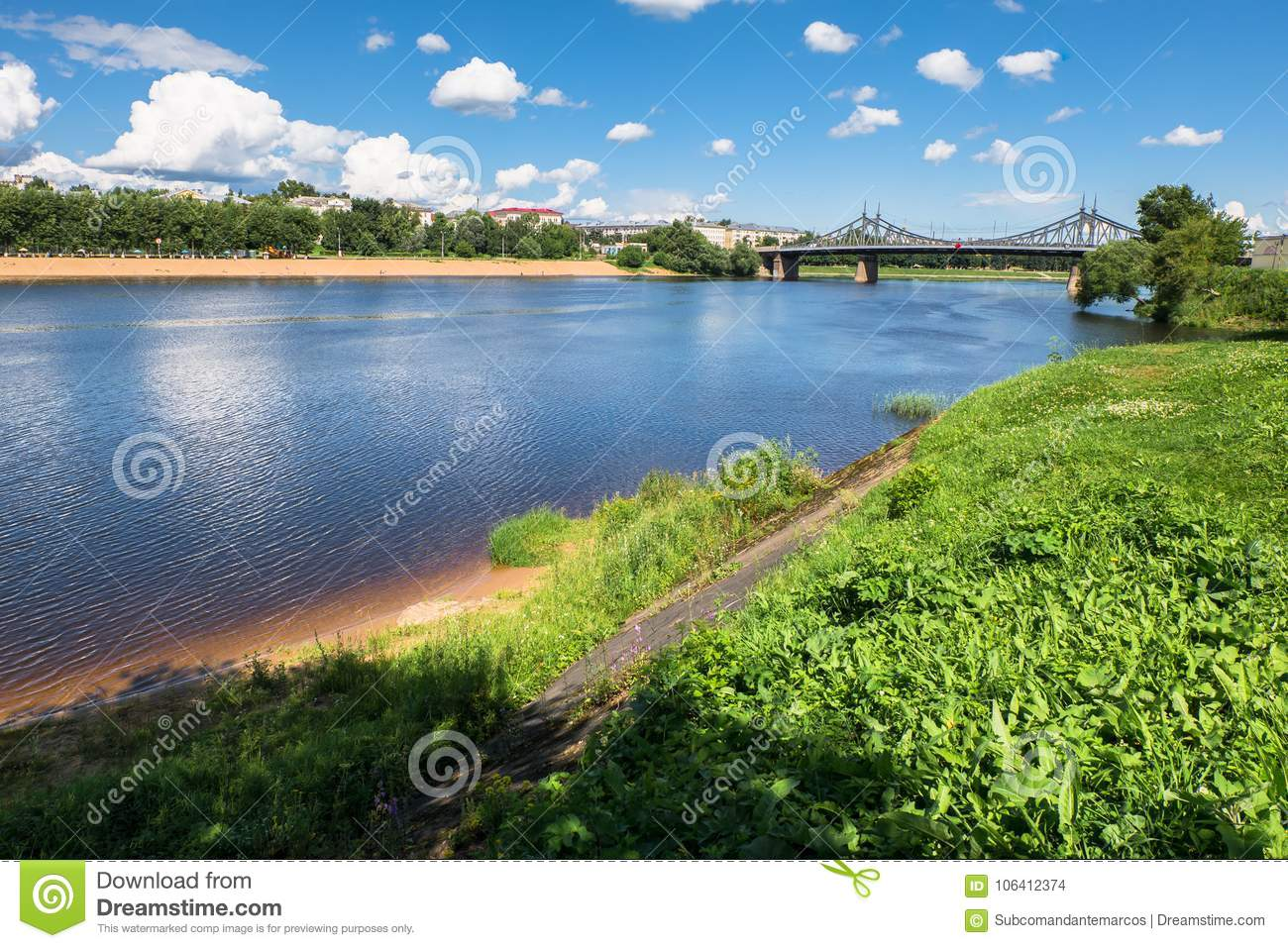 Summer view of the water surface and shores of the Volga river and the old Volga bridge in the background, city of Tver, Russia.