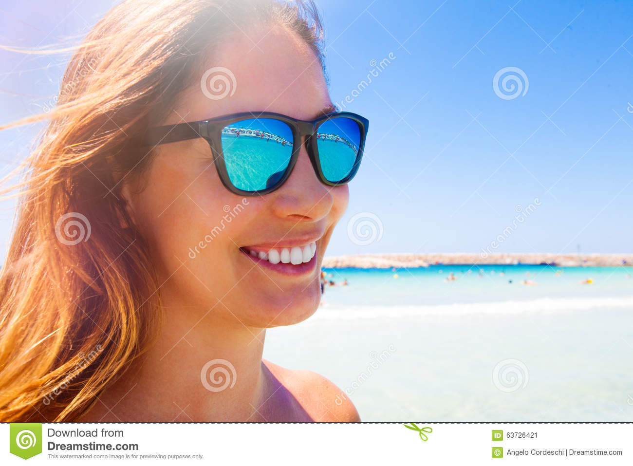 9db87248c15 Young and beautiful smiling woman with sunglasses. Blue sea in the  background. Beach holiday. Concept of fun and vacation. Sunbeam top