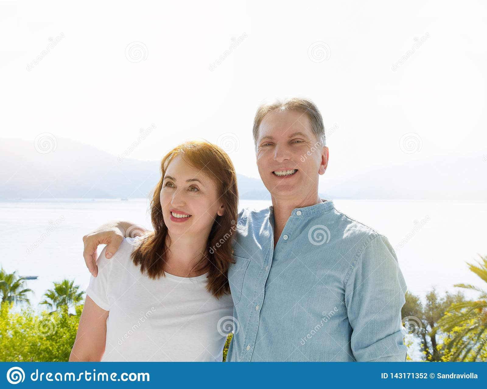 Summer white t shirt template. Happy middle aged family couple at vacation. Beach and holiday concept. Copy space and mock up