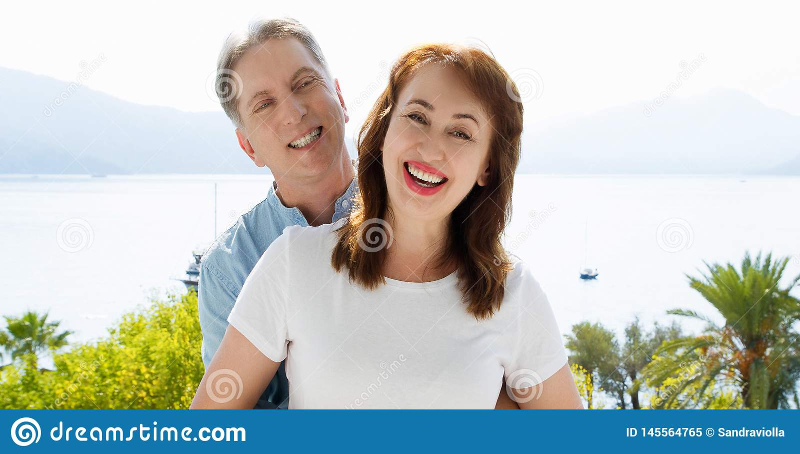 Summer white t shirt template. Happy middle aged family couple at vacation. Beach and holiday concept. Copy space and mock up.