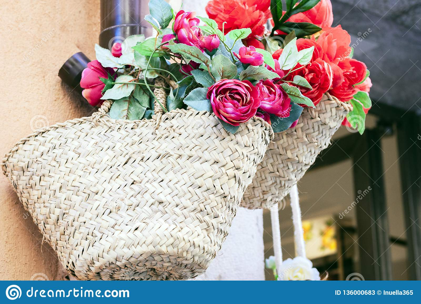 Summer wicker bags made of straw and rattan with textile flowers on the market in Taormina, Sicily, Italy