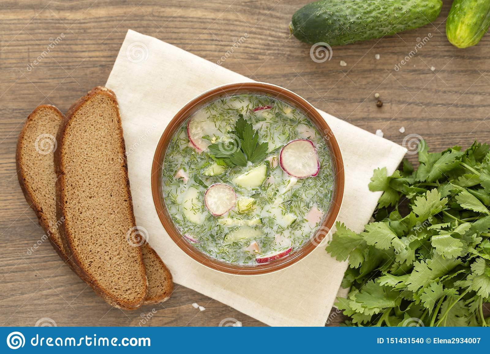 Summer yogurt cold soup with radish, cucumber, and dill on wooden table. Russian cold vegetable soup on yogurt.