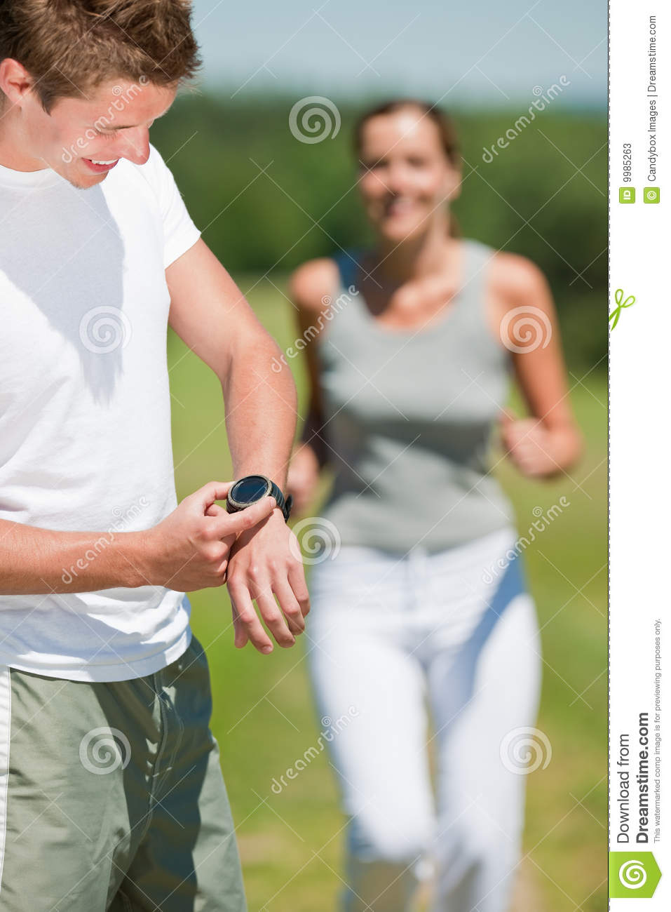 Summer - Young man with stopwatch measuring time
