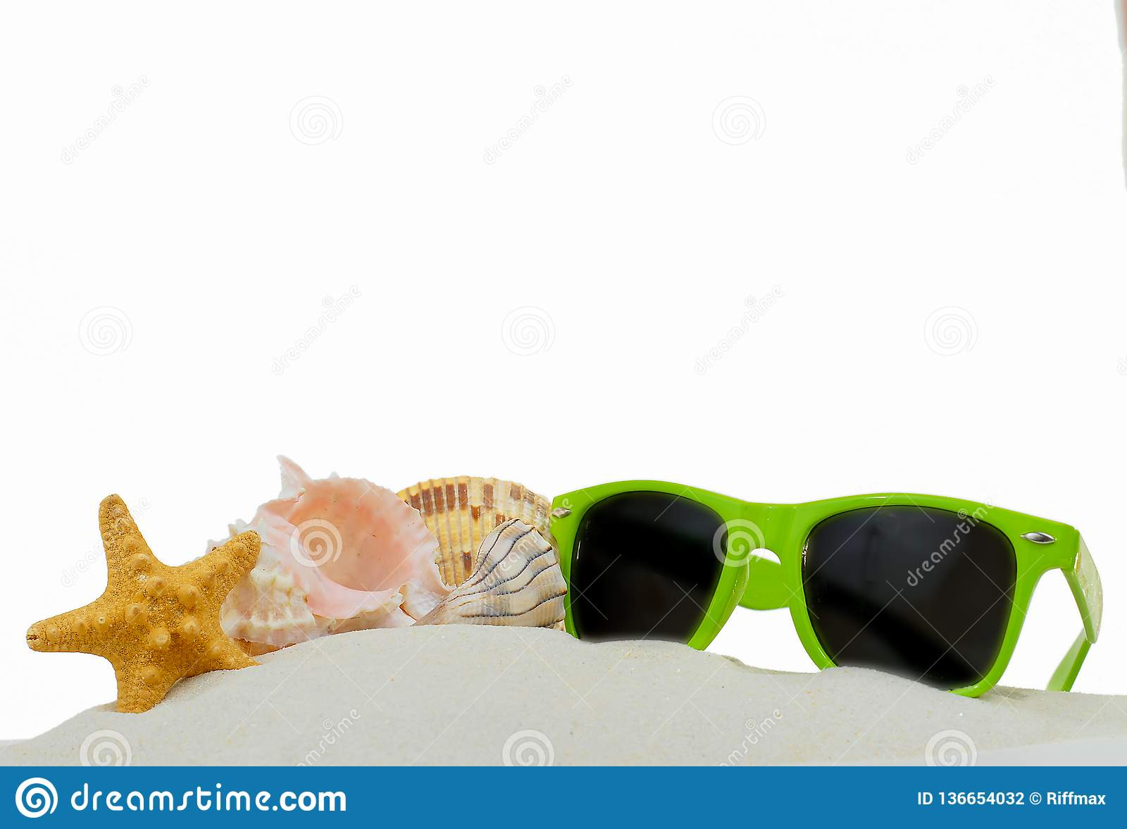 Summertime lower border image of starfish, shells and bright green sunglasses piled on sand. Isolated on white.