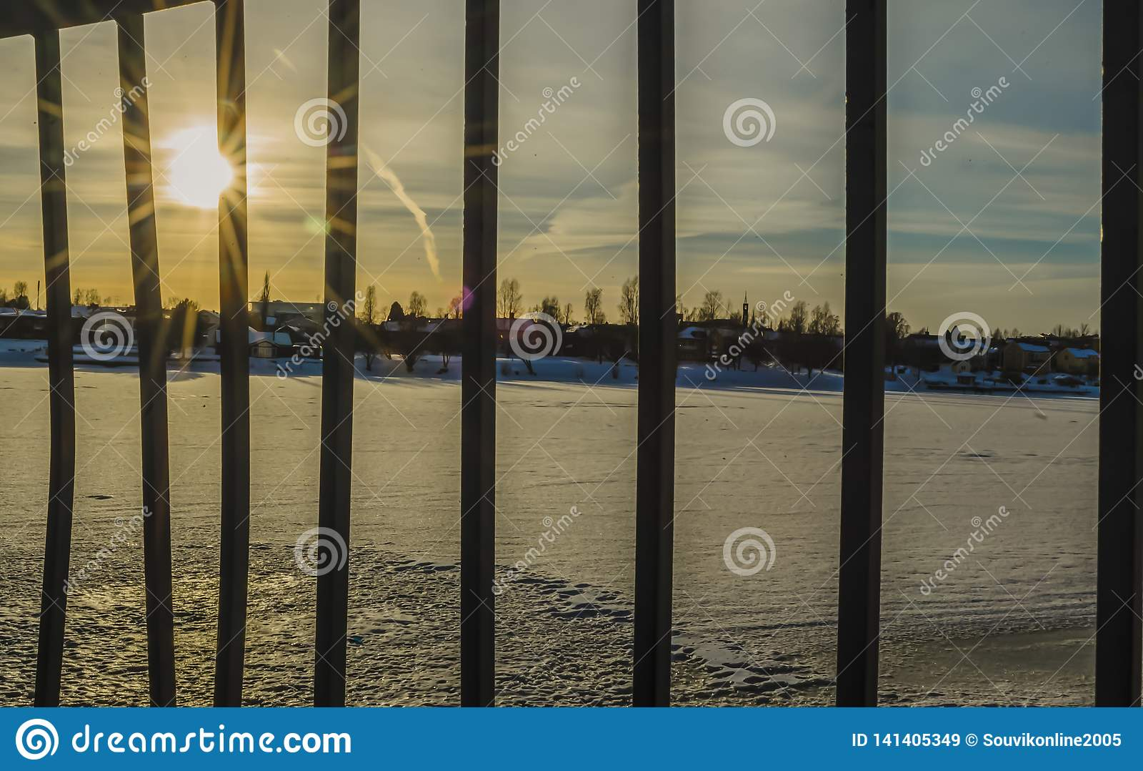 Sun alarga-se com os trilhos e a reflexão no rio congelado