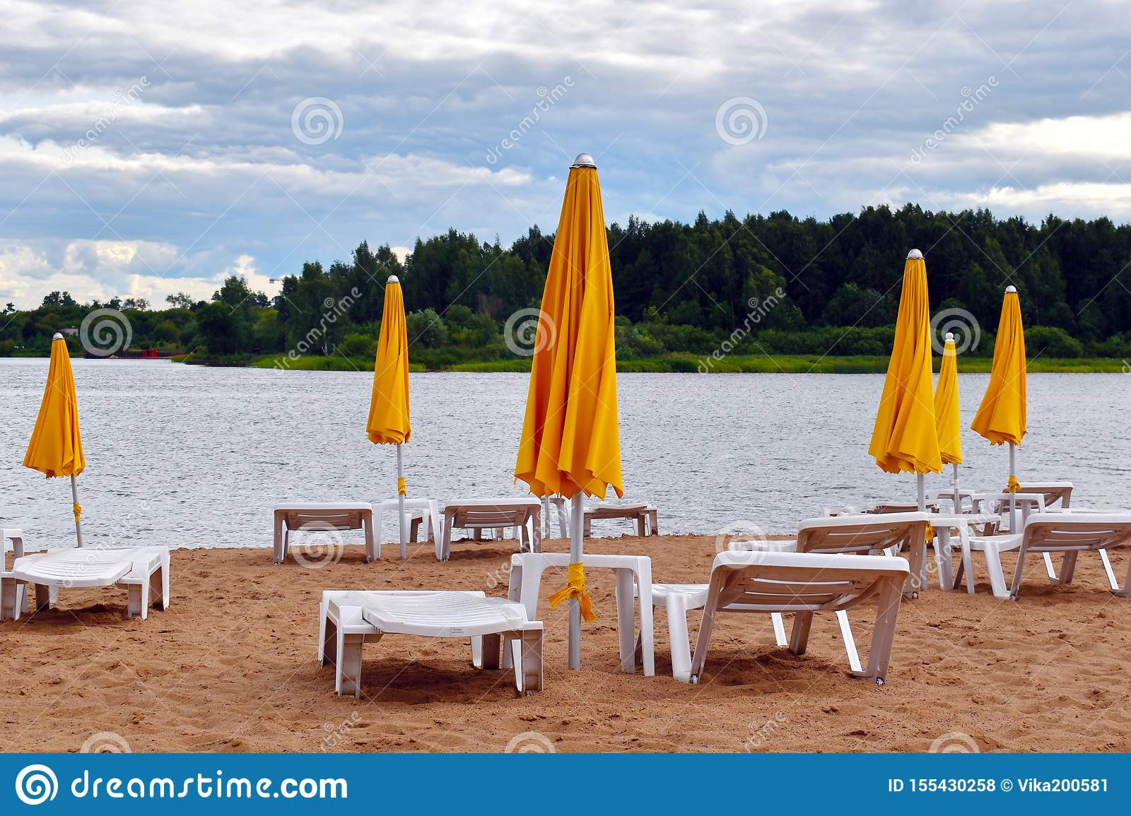Sun beds on the beach with yellow umbrellas in summer