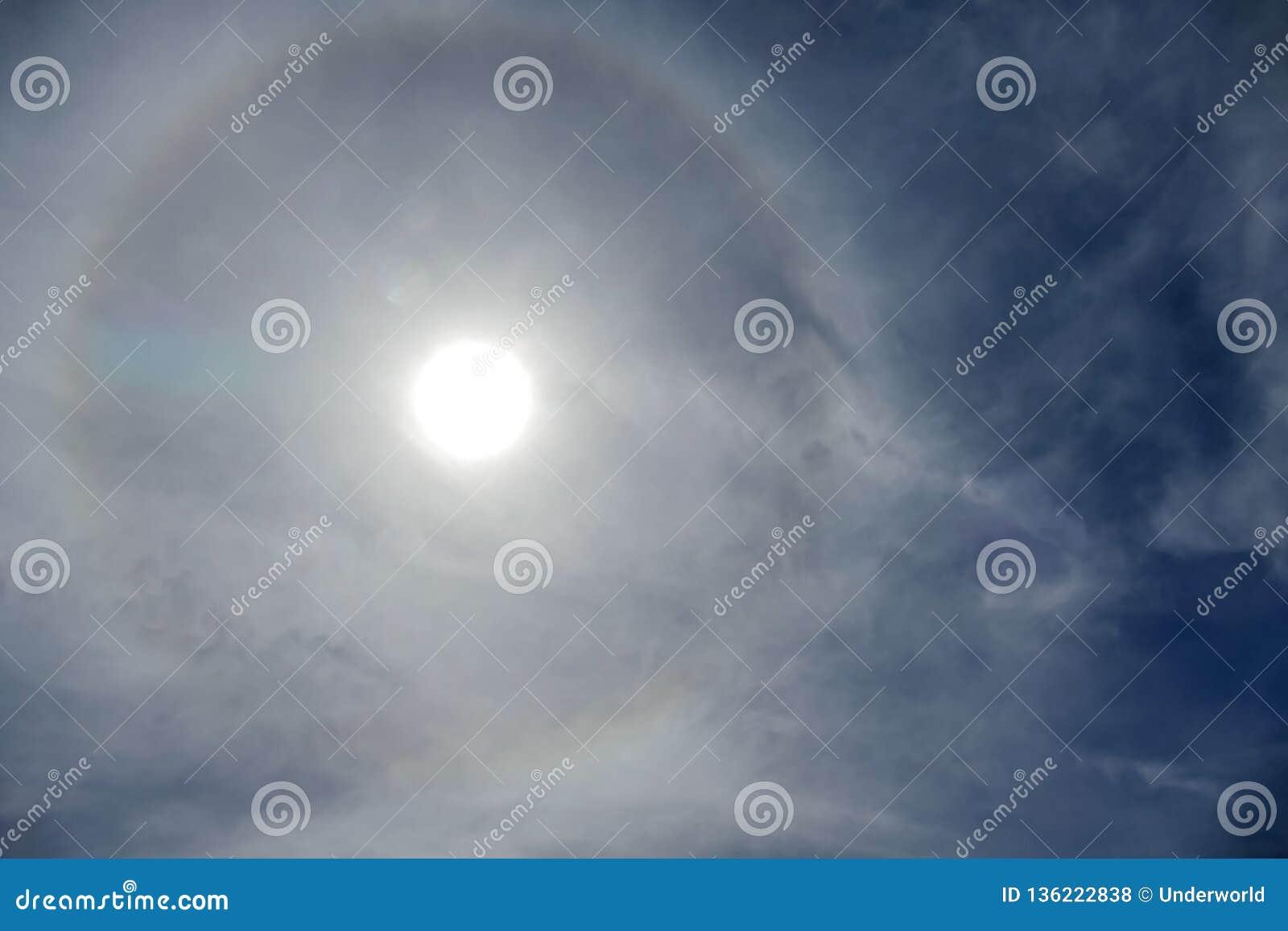 Sun con l avvenimento circolare di alone del sole dell arcobaleno dovuto i cristalli di ghiaccio in atmosfera, fondo di alone del