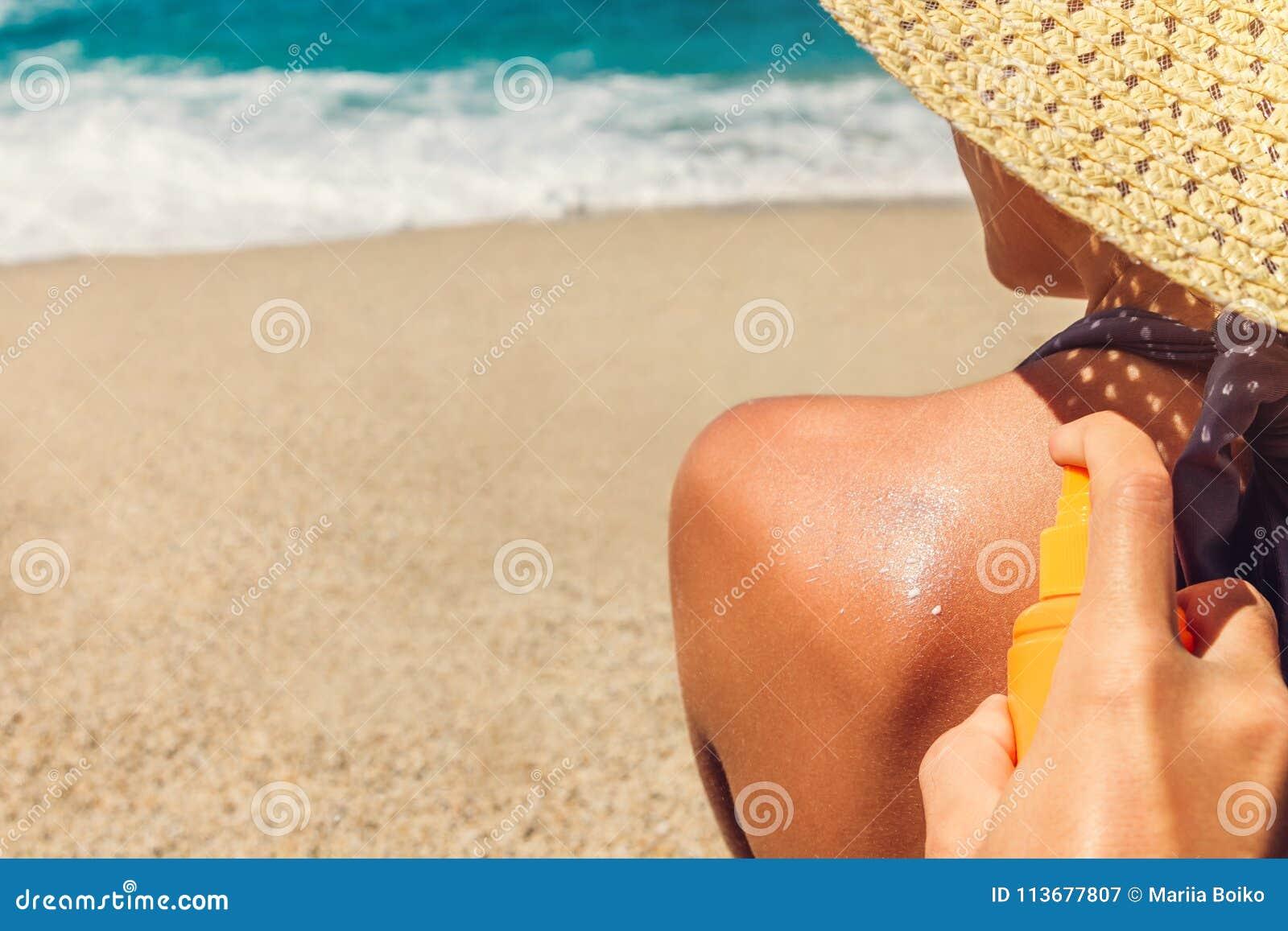 Sun cream protection. Man sprays sun cream on woman`s shoulder. Skin care concept. Healthy skin on vacation.