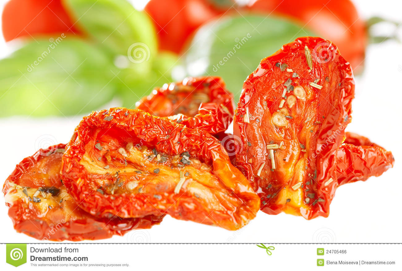 Sun-dried tomatoes with basil leaves and tomato on background, over ...