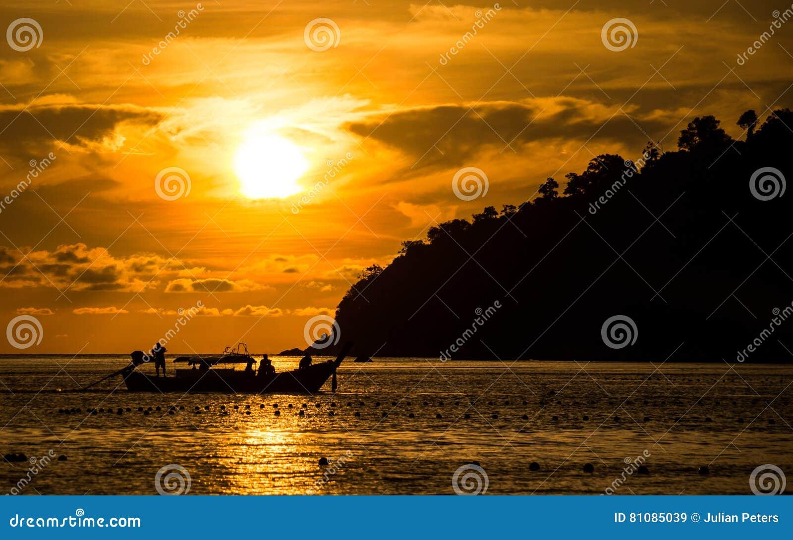 Sun-Einstellung hinter longtail Boot in Ko Lipe, Thailand