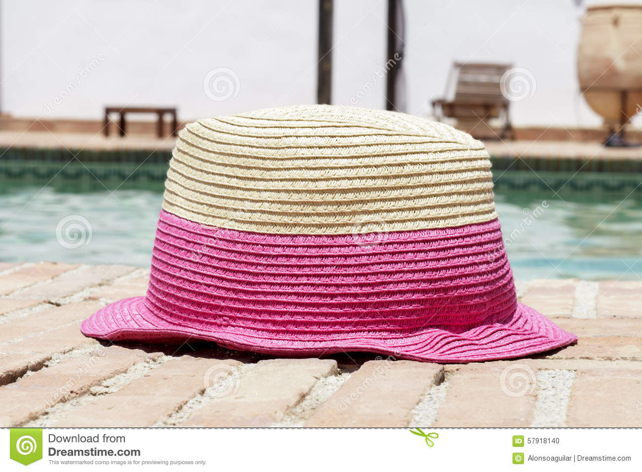 cf42e0b5 Close-up of a clear and pink sun hat in front of a swimming pool. Holidays