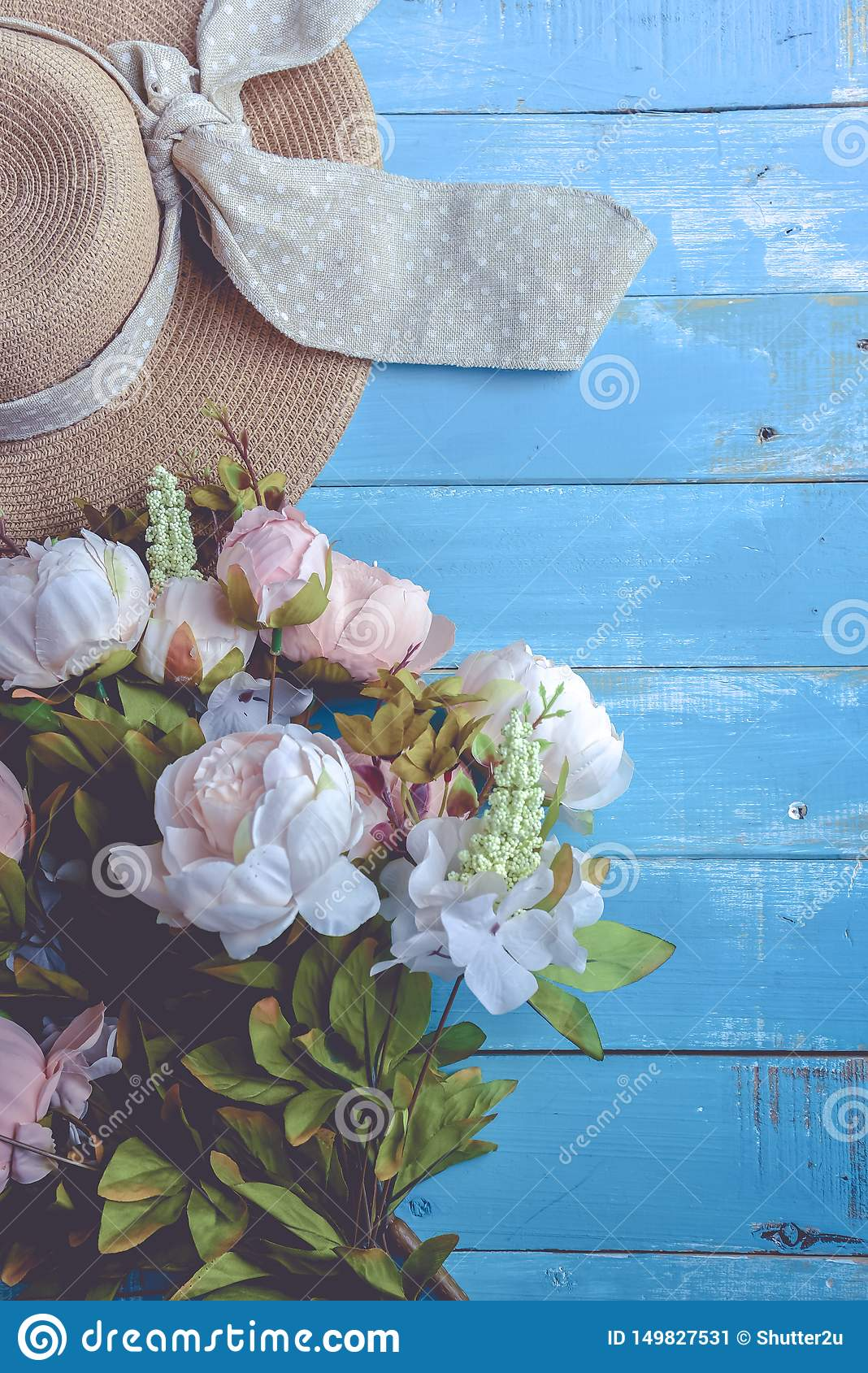 Sun hat and flowers on blue wooden plank background. Holiday and relax concept. Pastel tone