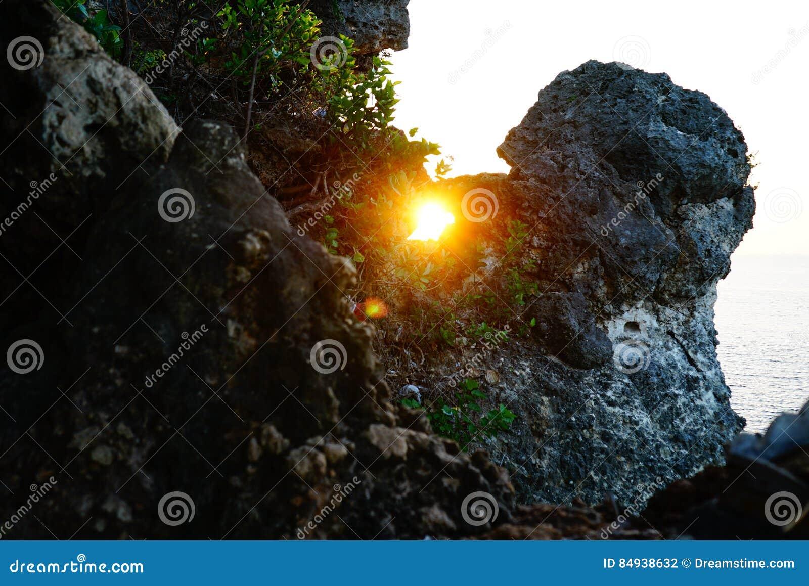 Sun innerhalb des Felsens durch das Meer