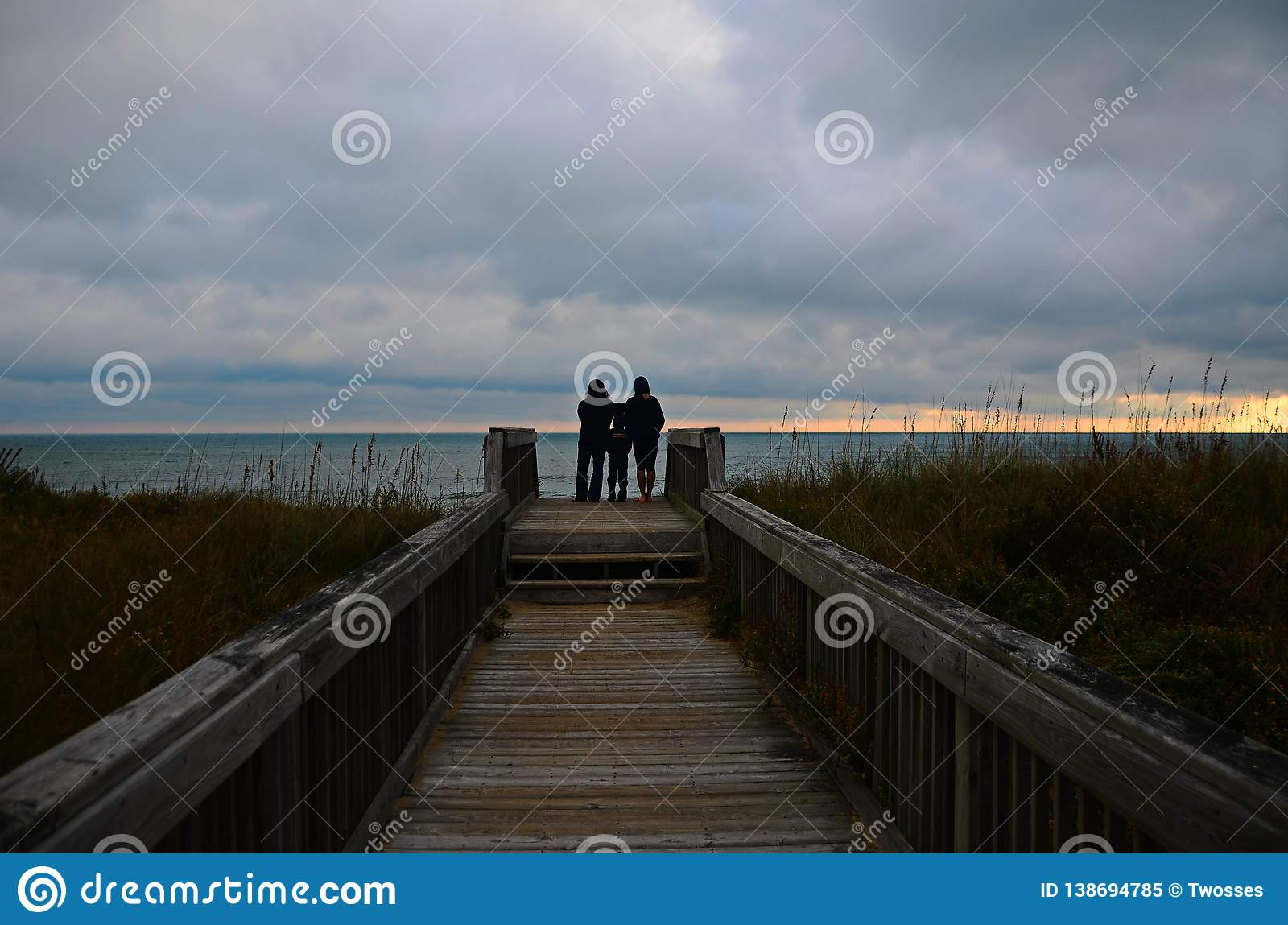 A family watches a sunrise at the beach