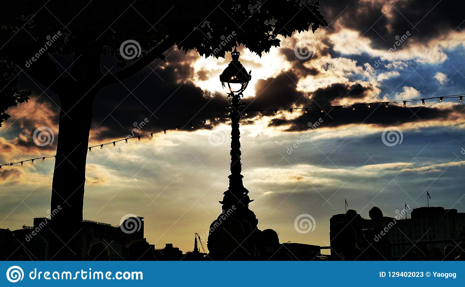 Sun in lamp post with clouds and silhouette. Dramatic blue colored sky picture with the sun in a lamppost, with tree, buildings and some clouds in silhouette stock photos