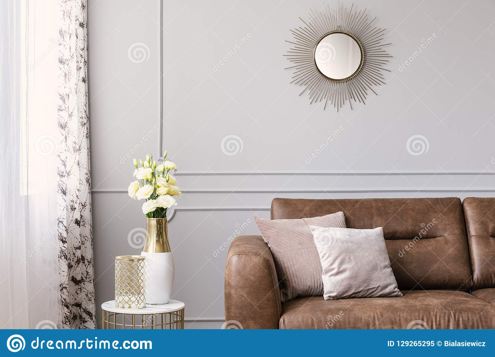 Sun like shaped mirror above leather sofa with pillows in grey elegant living room
