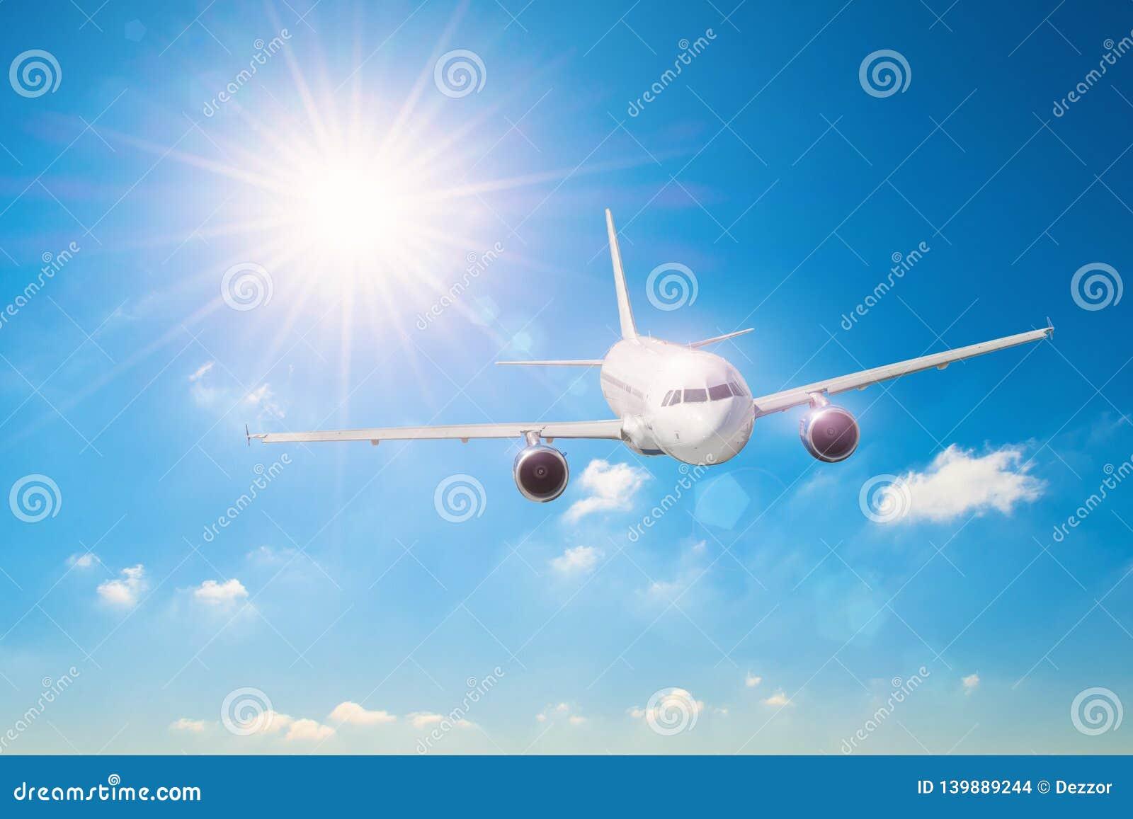 Sun mit hellen Strahlen im blauen Himmel mit weißen hellen Wolken, fliegendes Flugzeug, das im Urlaub reist