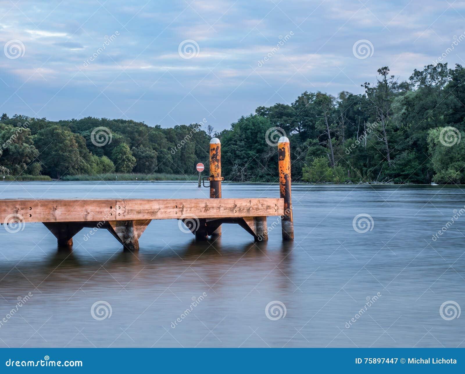 Sun que ajusta-se sobre um lago nas madeiras, no verão