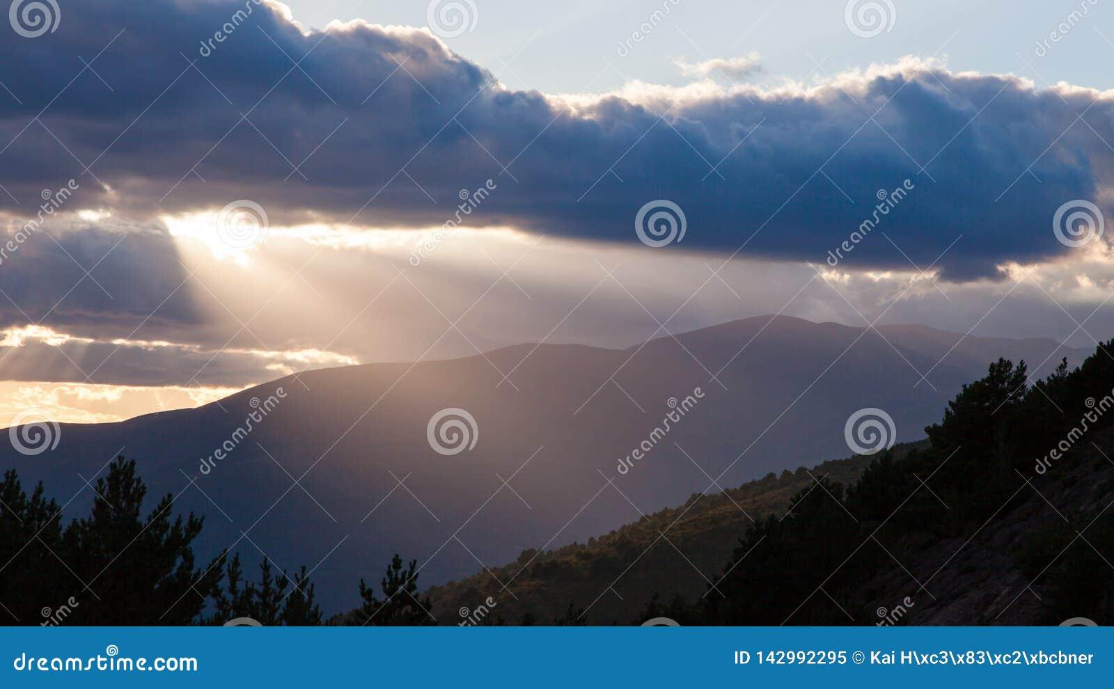 Sun que brilla a través de las nubes gruesas sobre las montañas justo antes de la puesta del sol