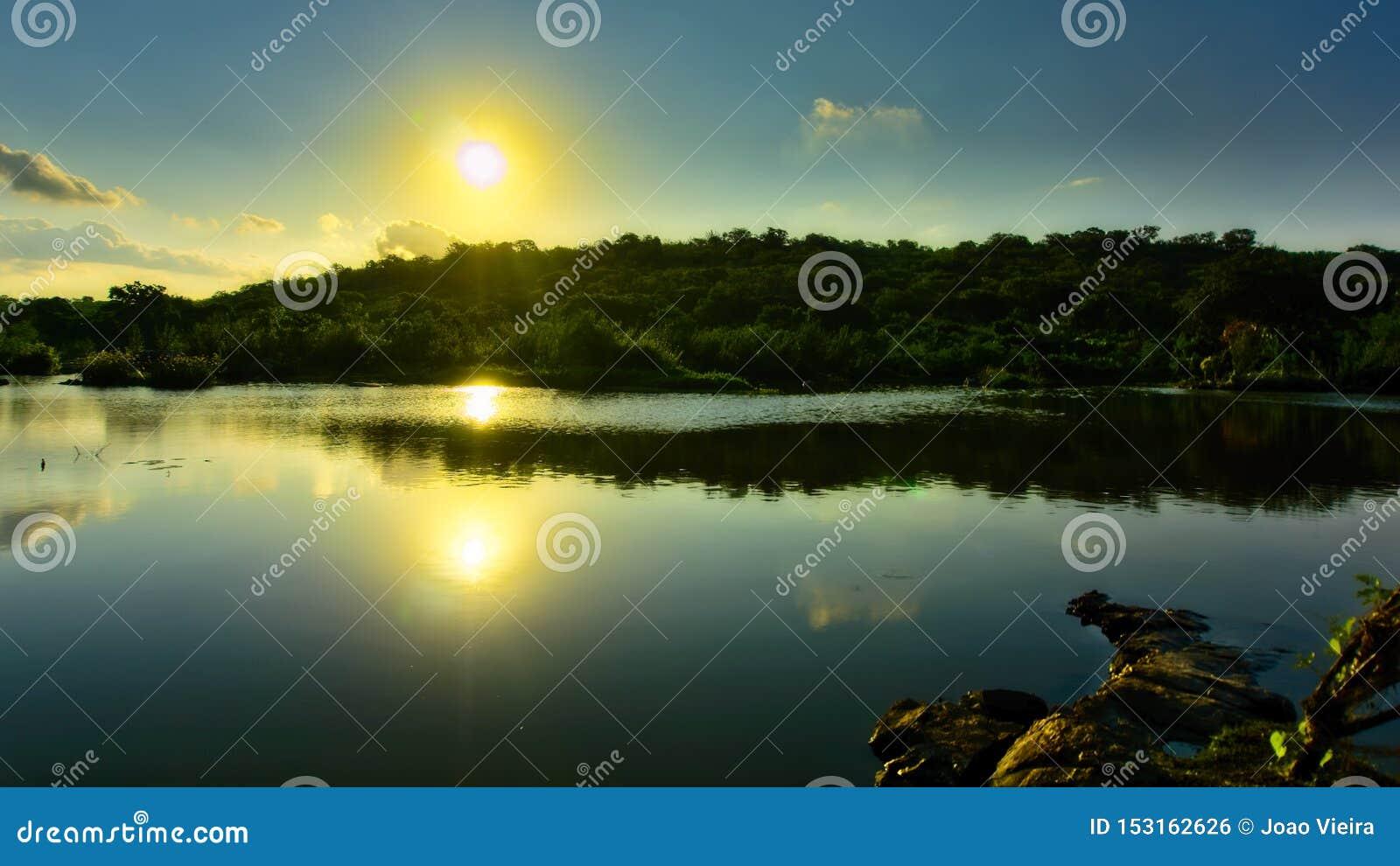 Sun reflejó en un río, Feira de Santana, Bahía, el Brasil