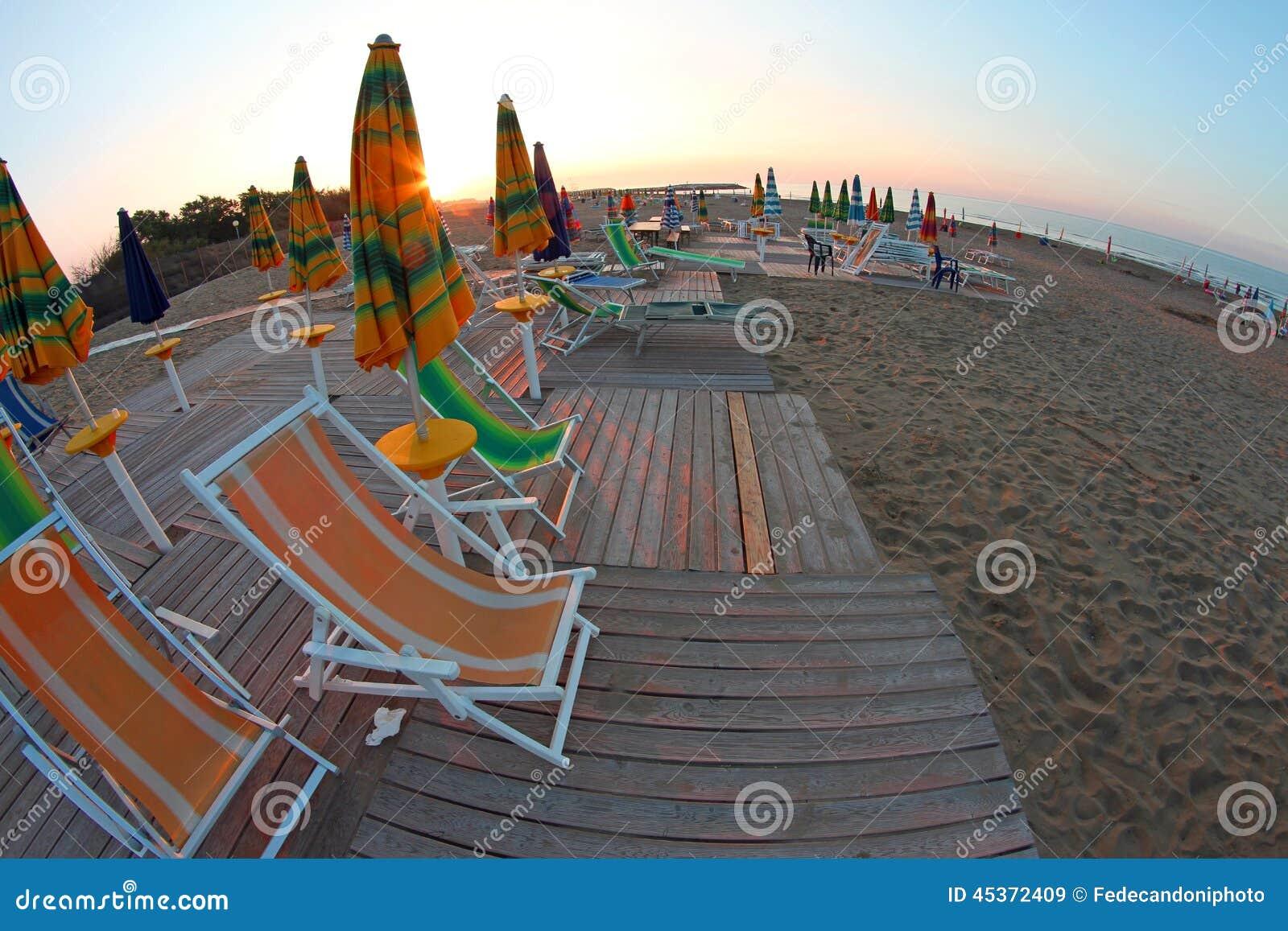 Sun se lève sur la plage toujours abandonné, avec les parasols a