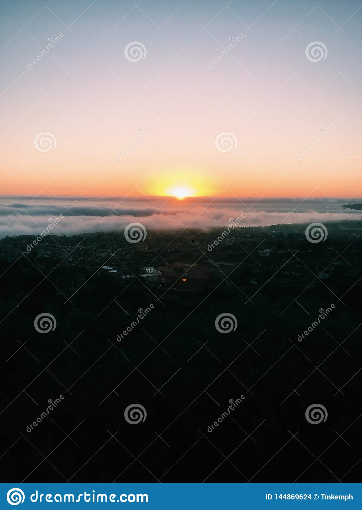 Sun setting behind a layer of clouds