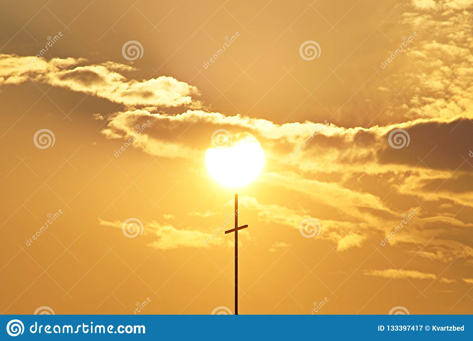 Beautiful sunset through the clouds with cross catholic