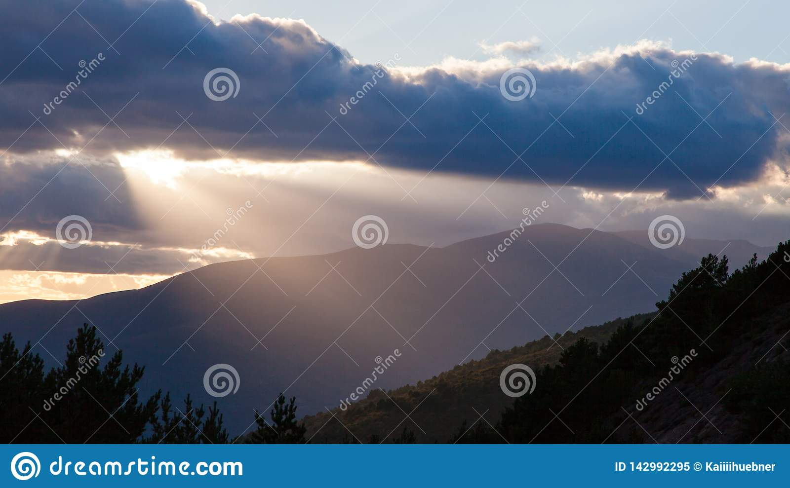 Sun shining through thick clouds over mountains right before sunset.