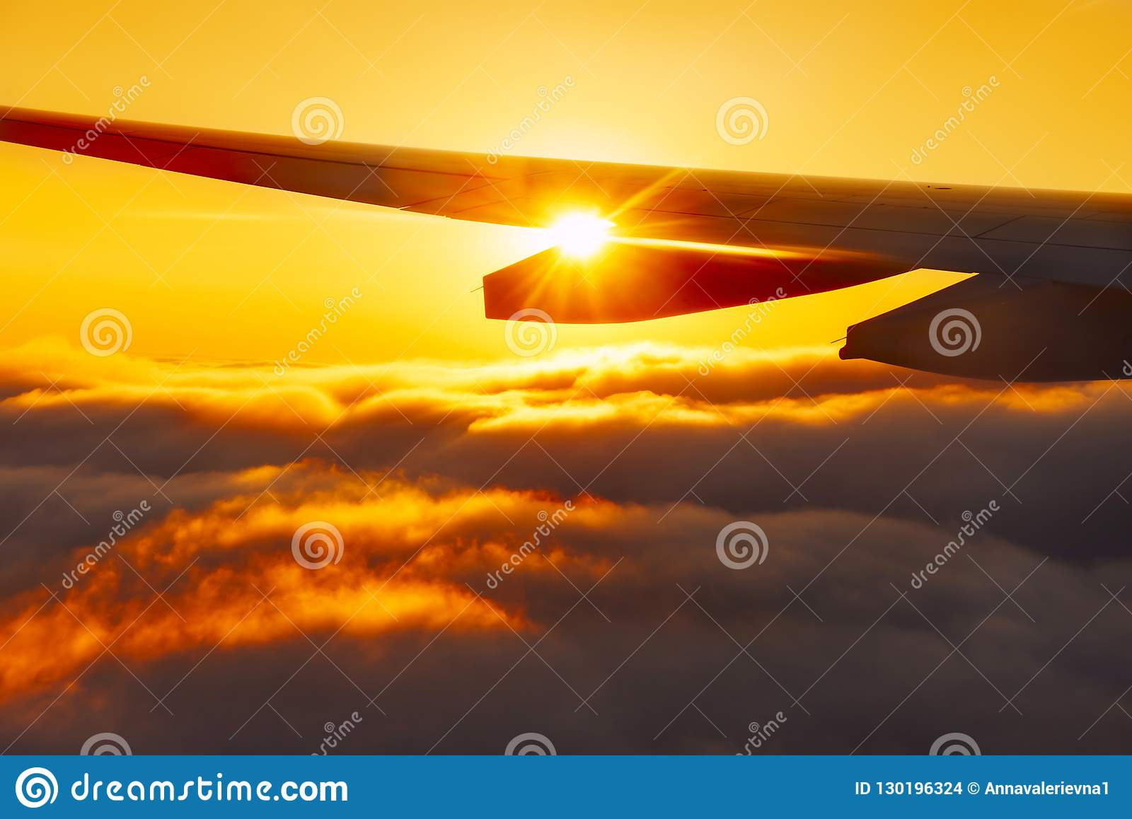 The sun is shining through the wing of the plane above the clouds in flight at sunset. The atmosphere of travel and vacation.