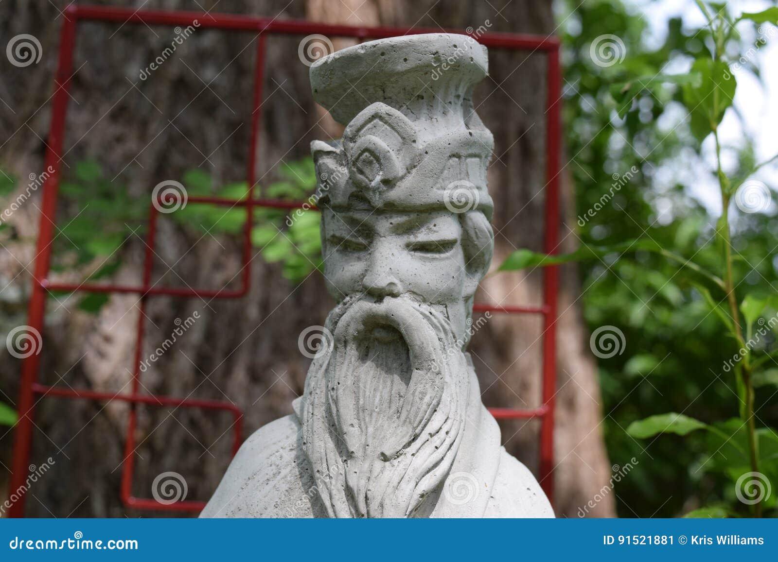 Sun Tzu statue in front of red garden arbor