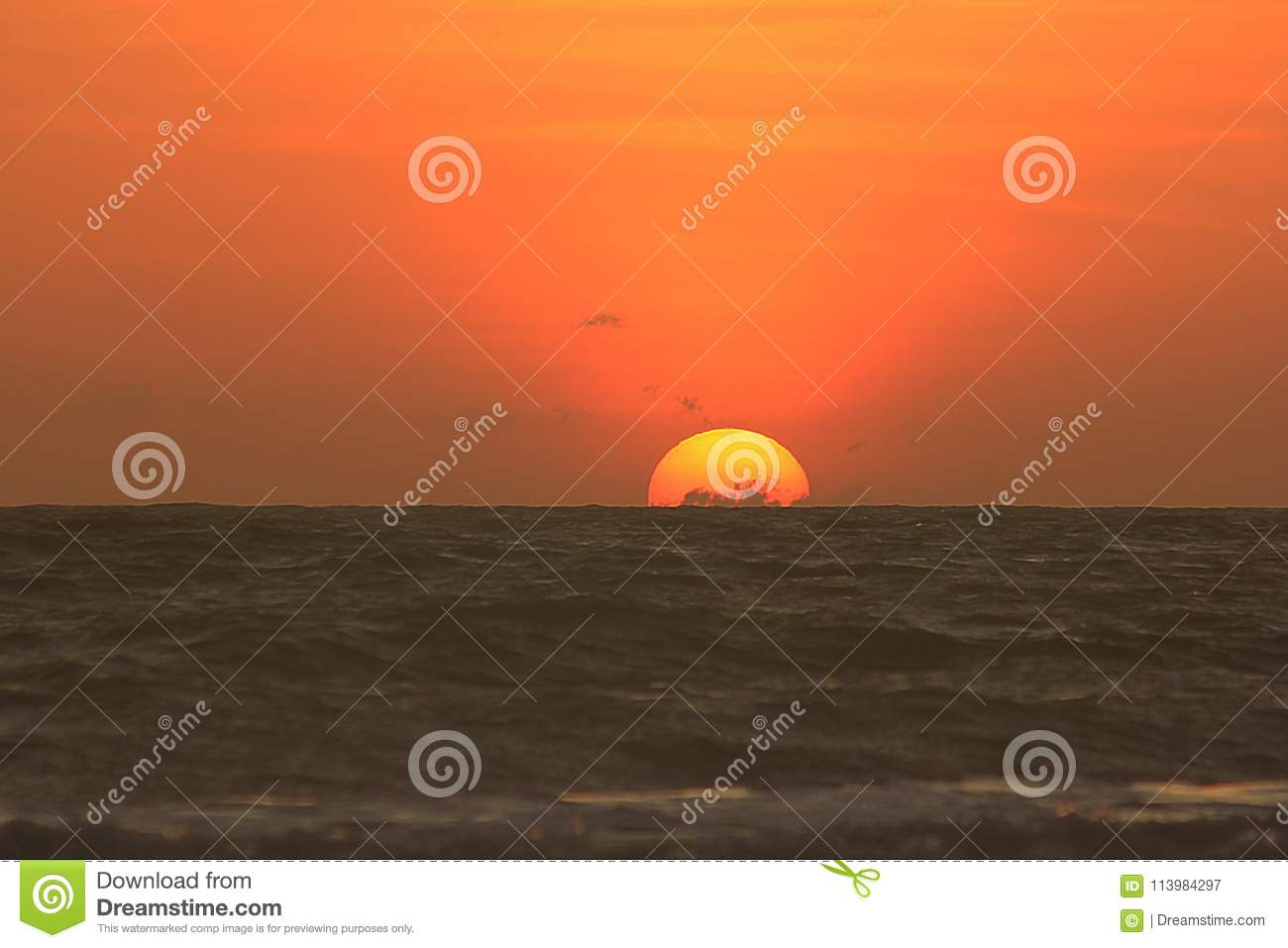 The sun is rising in the morning from the sea.
