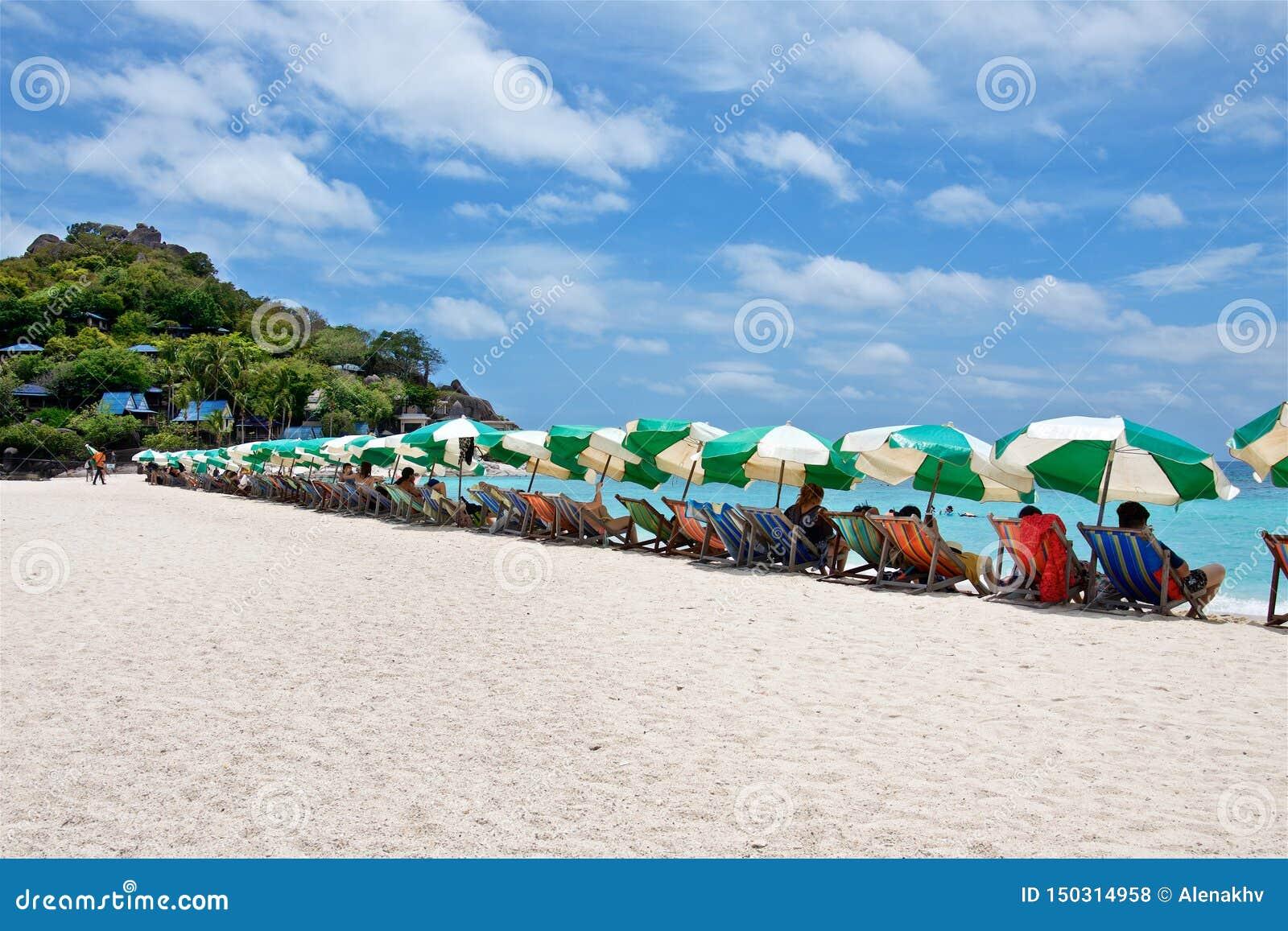Sun umbrellas and deck chairs on a white beach of Nang Yuan island