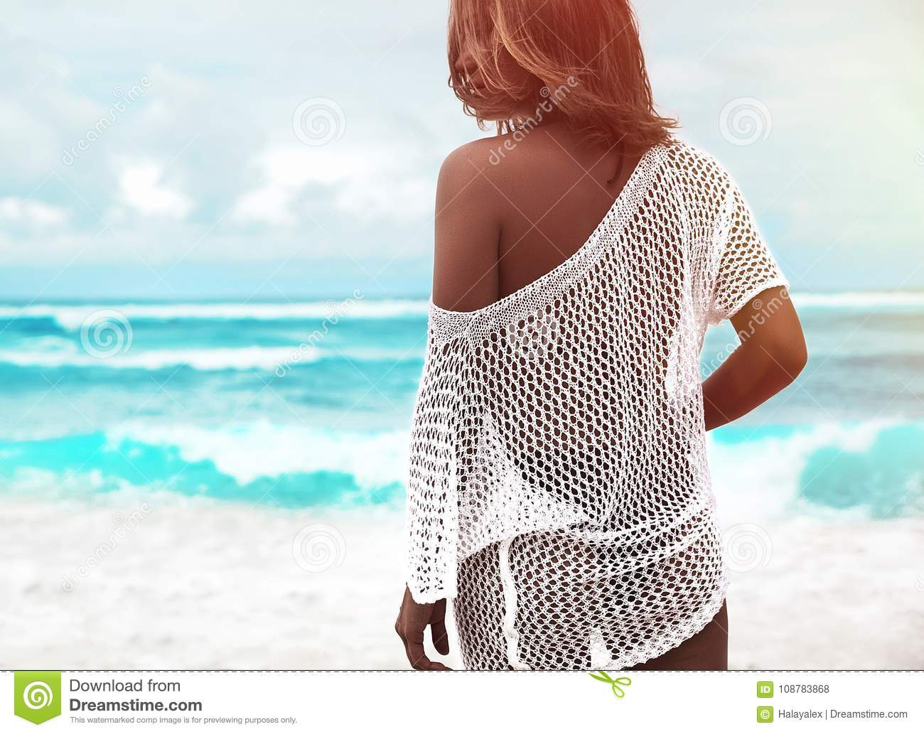 Sunbathed woman model in transparent white blouse sitting on summer beach and blue ocean background