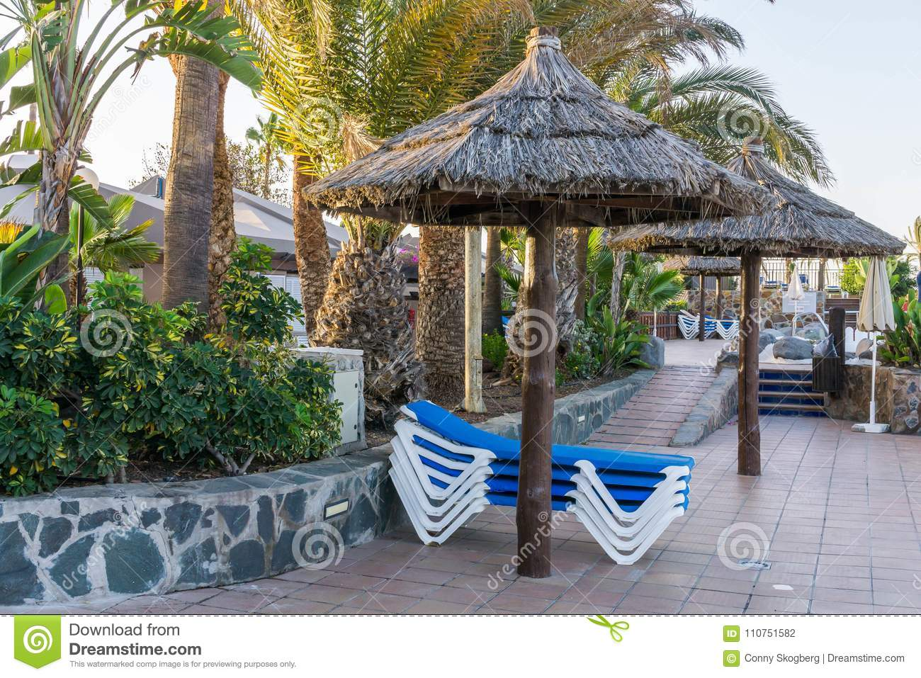 sunbathing area at hotel bungalows sun beds blue and white beneath an umbrella