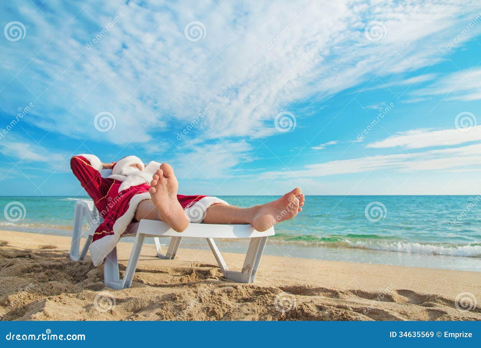 Sunbathing Santa Claus relaxing in bedstone on tropical beach