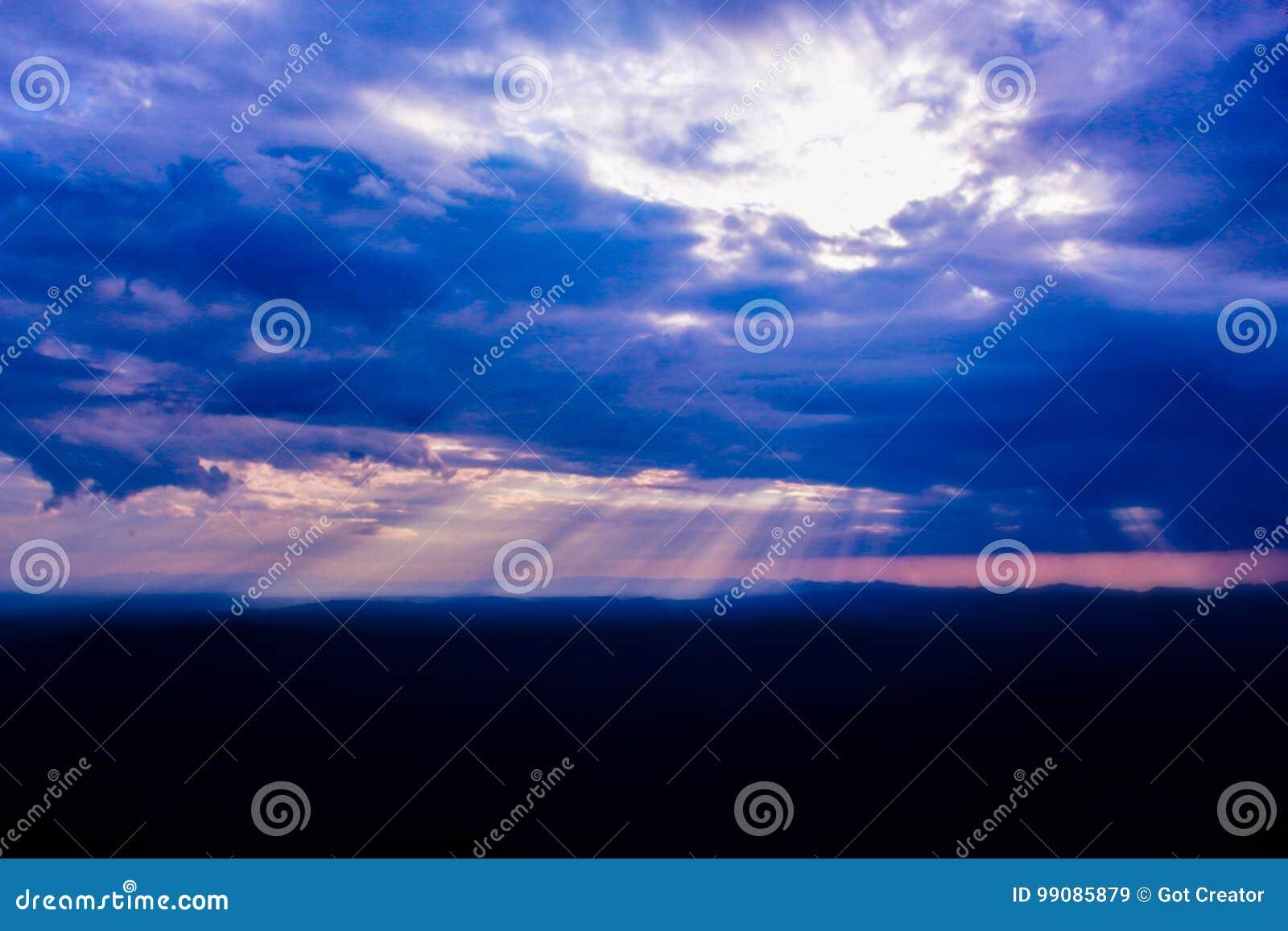 Sunbeam through clouds on blue sky.