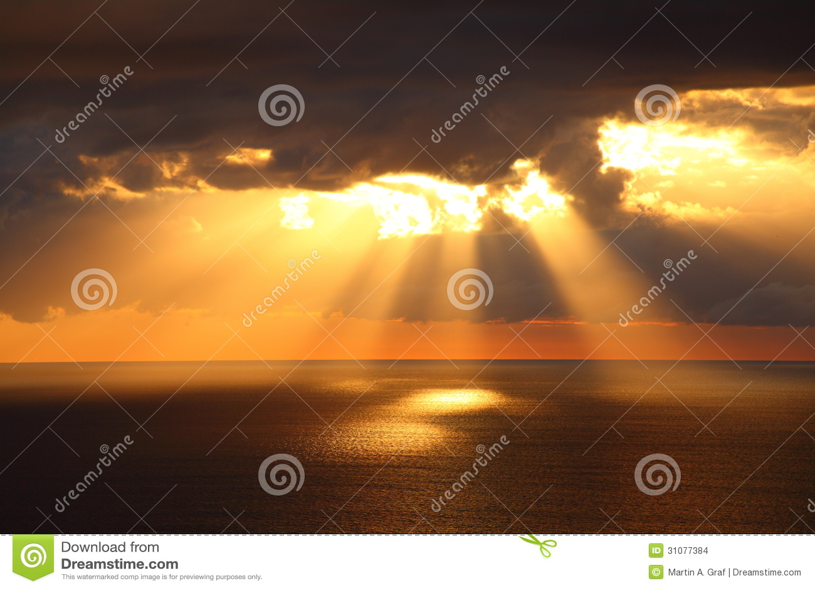 Sunbeams through dark clouds over ocean