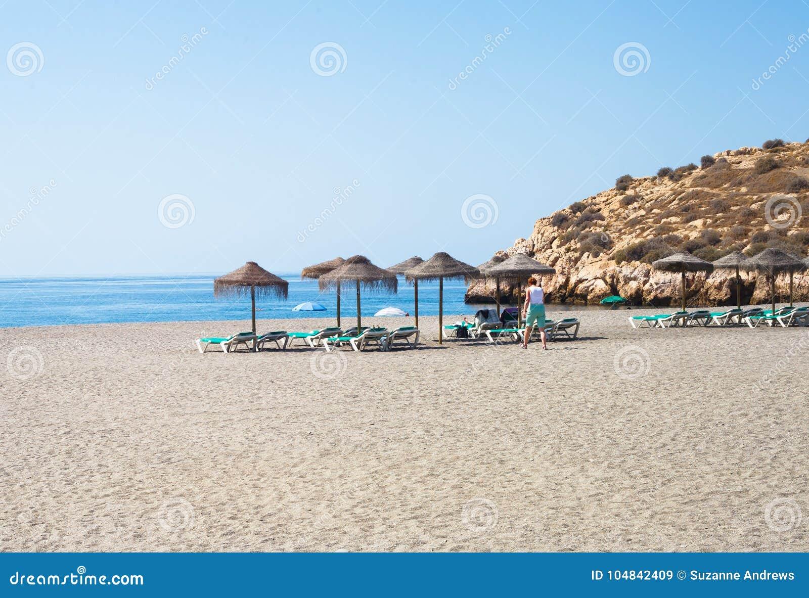Sunbeds и зонтики соломы на пляже