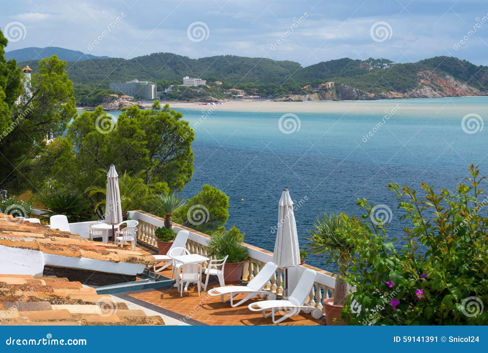 Sunbeds do terace da casa de campo de Hause do verão no lado de mar de Mallorca