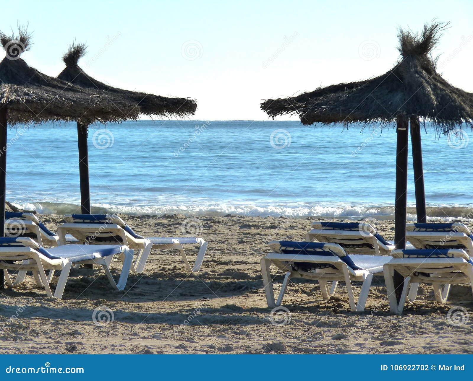 Sunbeds i parasole na pustej plaży w Hiszpania