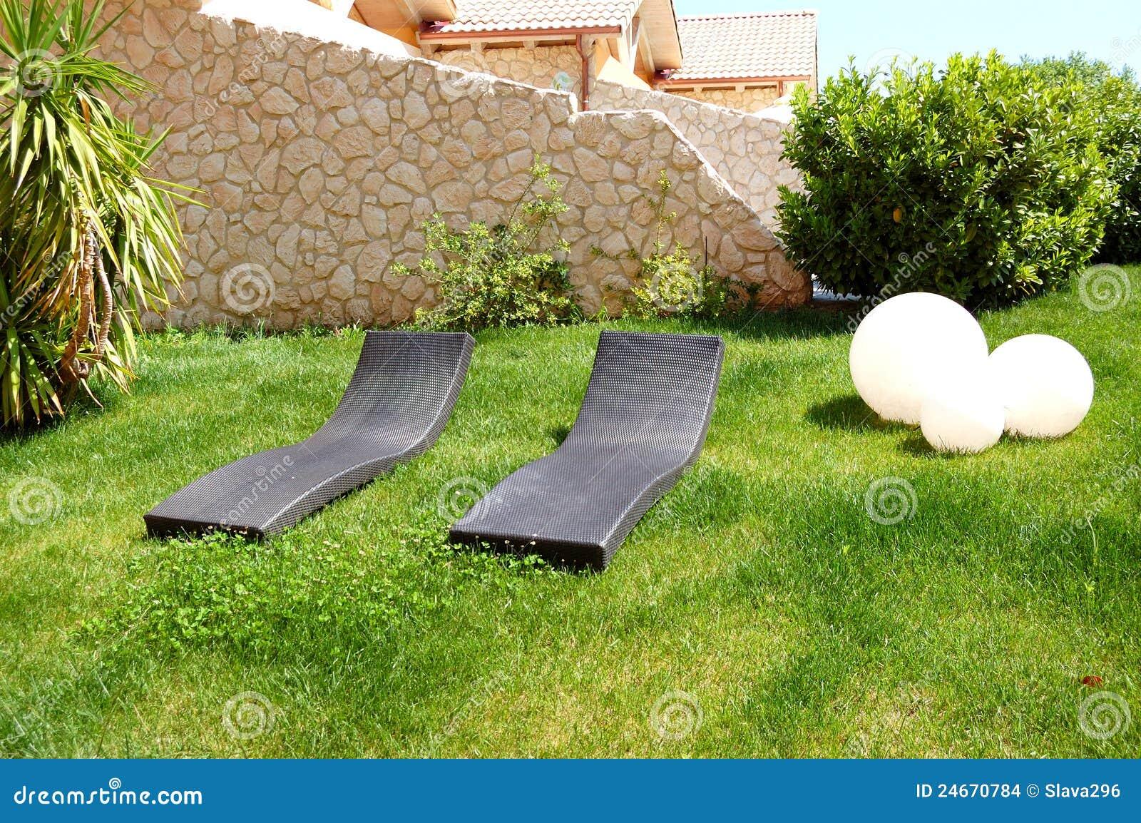 Sunbeds on lawn by luxury villa